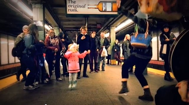 Une fillette fait le show dans une station de métro.