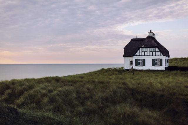 house on coastline at sunset